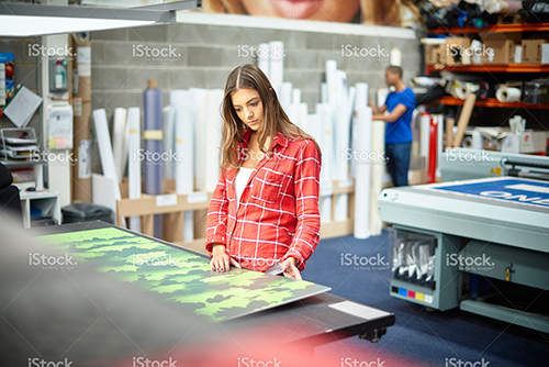 stock-photo-77979801-young-woman-working-at-a-signage-company